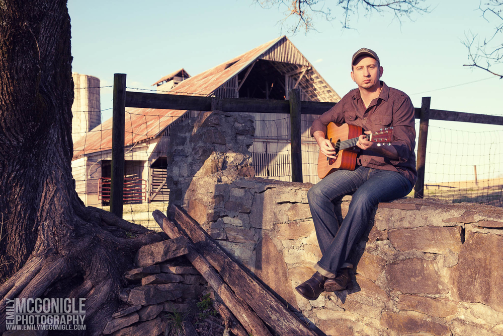 man on a stone wall with a guitar