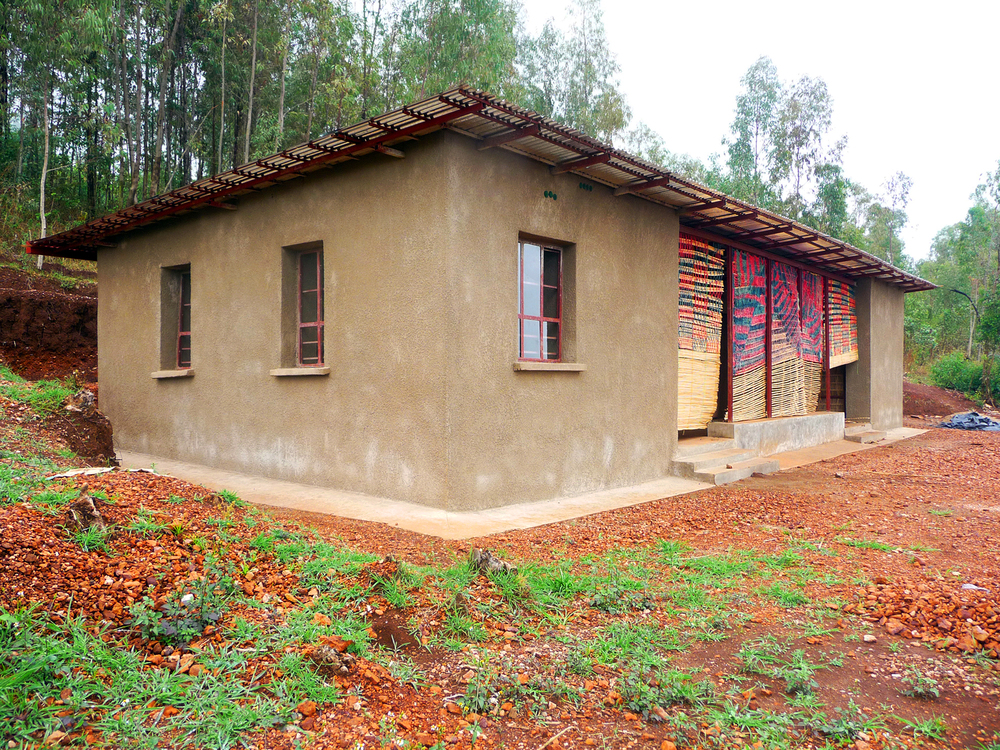 The first Earthbag house close to completion. Local artisans created woven screens that protect porches and exterior living spaces.