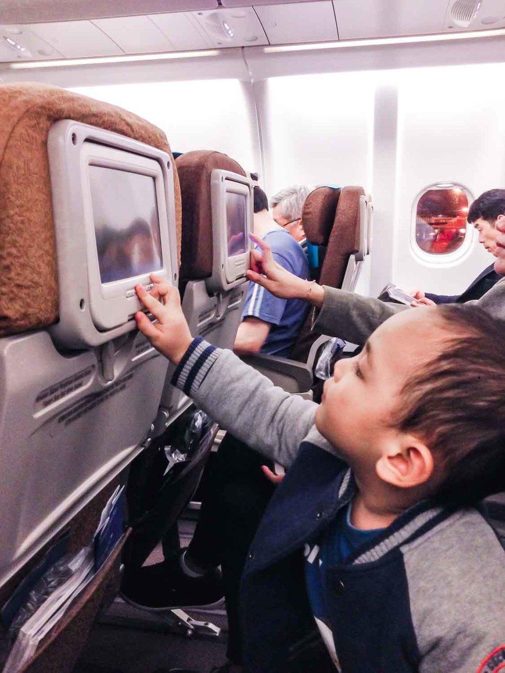 Hugo bermain-main dengan layar di pesawat, banyak film anak-anak jadinya dia betah :)