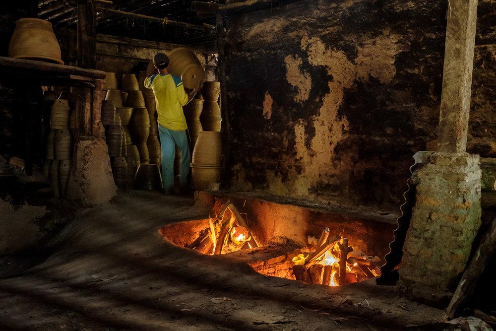 Pengrajin sedang mengangkat gerabah kering yang siap dibakar.