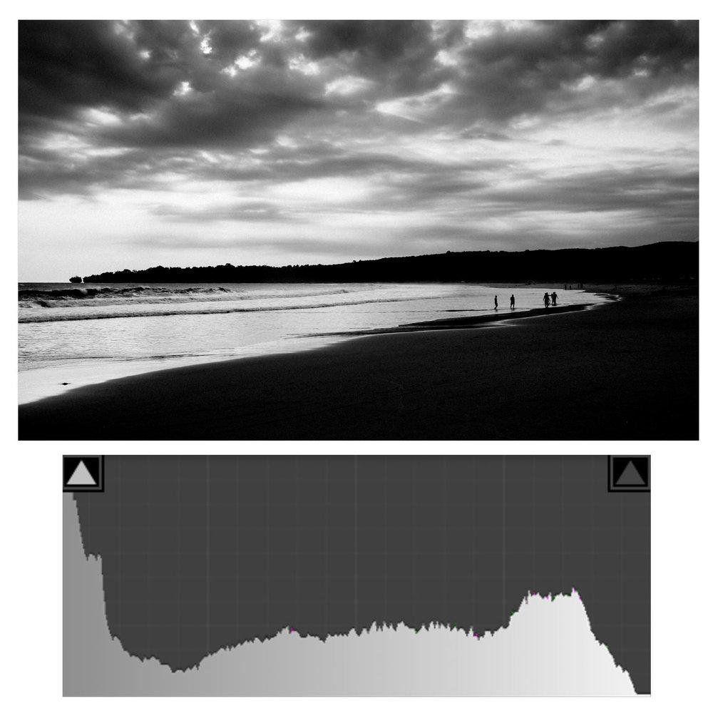Bagian bukit, siluet manusia, dan sebagian pantai sudah tidak mungkin dikembalikan detailnya. Terlihat di histogram piksel sudah melewati batas kiri.