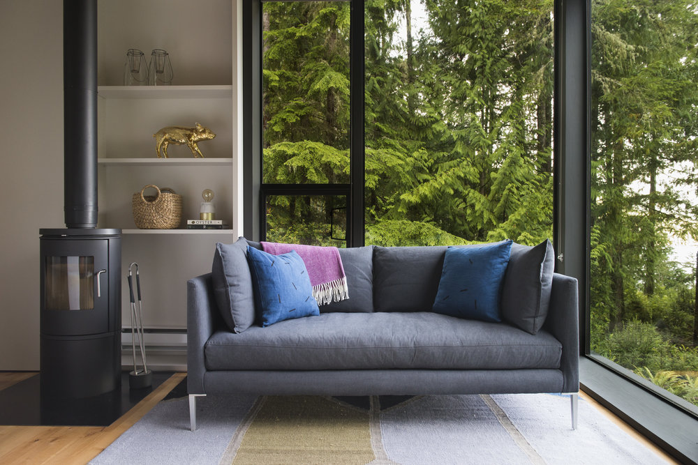 Avery Cox Design- Washington State- In the living room, a bench seat sofa nestles in among the trees