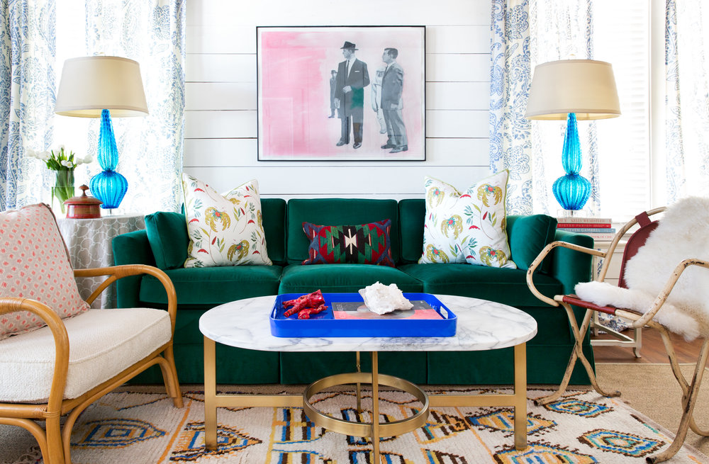 Avery Cox Design- Austin Texas East Side Bungalow features a jade green velvet sofa, blue Murano glass lamps, original art, Moroccan rug, and vintage rattan.