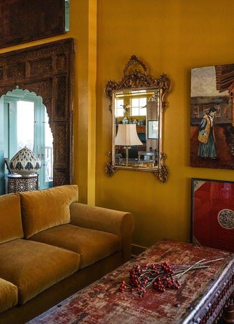 Elizabeth Vallion Interiors Saffron yellow living room with velvet sofa and moorish doorway