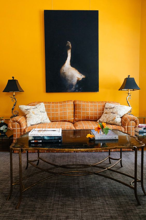 Cloth and Kind saffron marigold yellow living room with window pane check sofa yellow walls a black goose painting and gilt coffee table