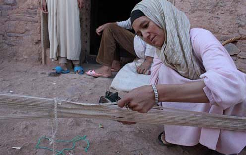 Weaving on a very simple and small loom laid on the ground. Photo :  SOAS Brunei Gallery