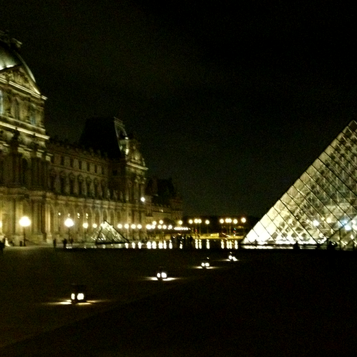 I.M. Pei's pyramid in the courtyard at the Louvre lit up at night makes for good bike riding, my favorite thing to do.