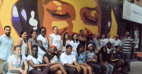 The JLL volunteers and CAW Youth Apprentices and teaching staff at the West Harlem Group Assistance Mural, which is adjacent to City Council Member Mark Levine's district office.