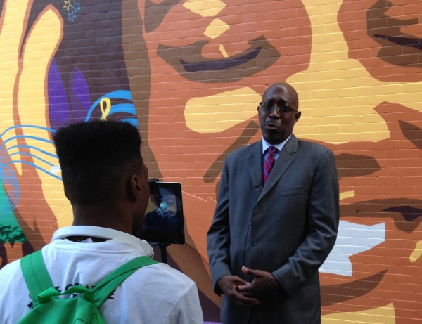 Youth Apprentices from the Multimedia Team interview Executive Director  Donald Notice  of West Harlem Group Assistance, at the unveiling of the 2015 mural,  Harlem Melody .