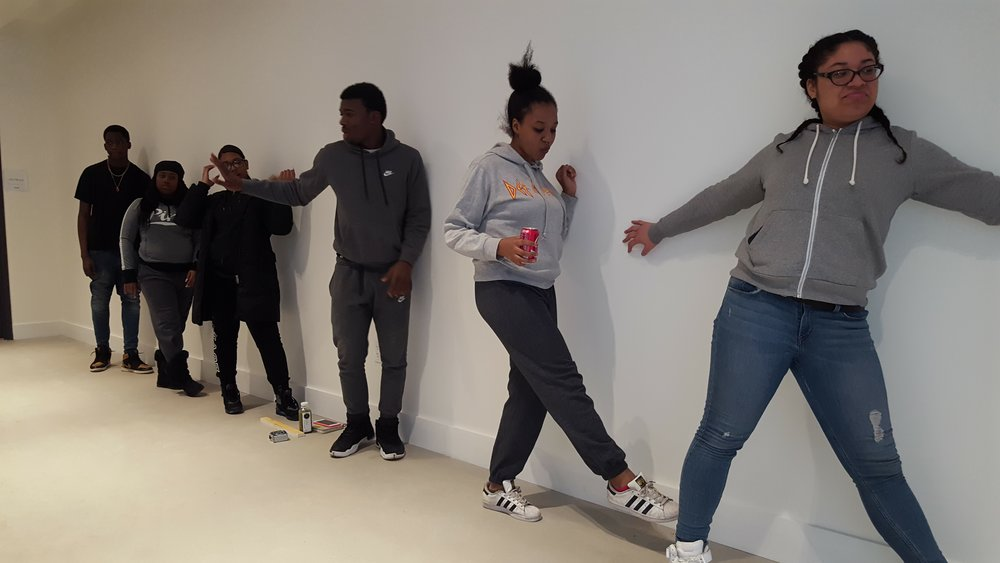 CAW Youth Apprentices block out their poses on the blank wall.