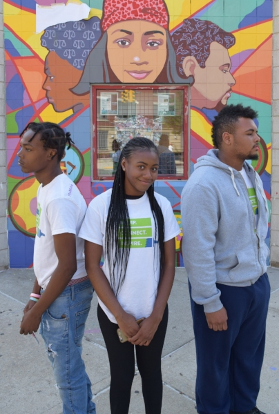 Donovon Jones, Cyrell and Aaron Clifford in front of their portraits