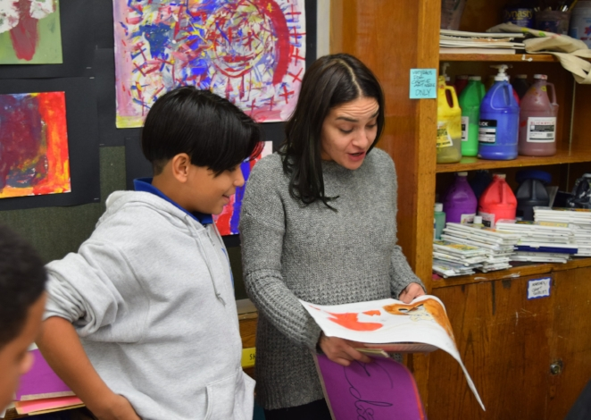 CAW Teaching Artist Yazeem Collazo critiques the work of a Hamilton Grange Middle School Student.