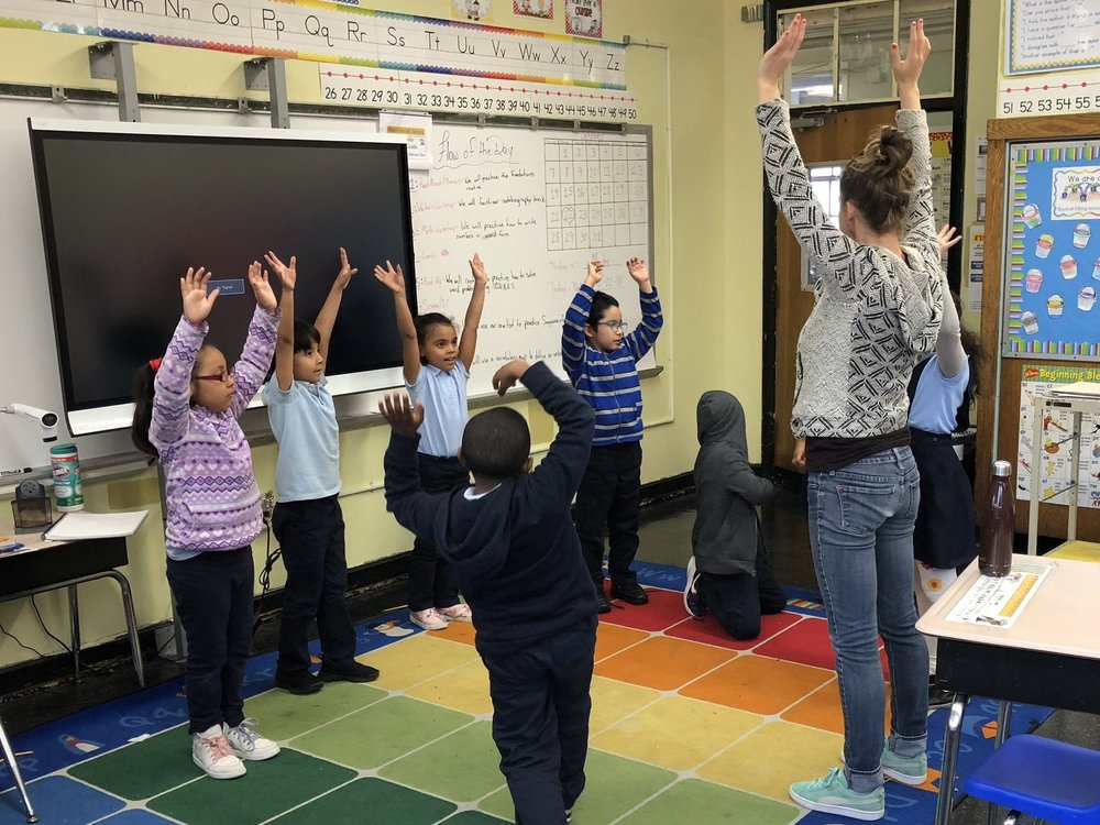 """""""Be a tree!"""" Stretching and movement games help second-graders burn off excess energy before sitting down to make art."""