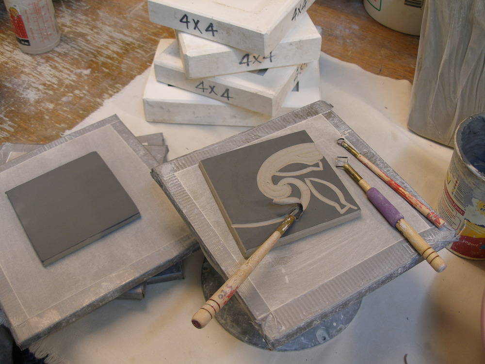 The blank tile is brushed with a layer of black colored clay, or slip, and once the slip has dried, stacked between boards to firm up overnight. When the tile has reached the leather-hard stage, still pliable, but easily retaining it's shape, it is ready to carve. The design is done free-hand, using a variety of looped cutting tools to remove the background, leaving the design. The carved tile is then stacked again between boards and left to dry for at least a week before it is dry enough for the bisque firing.