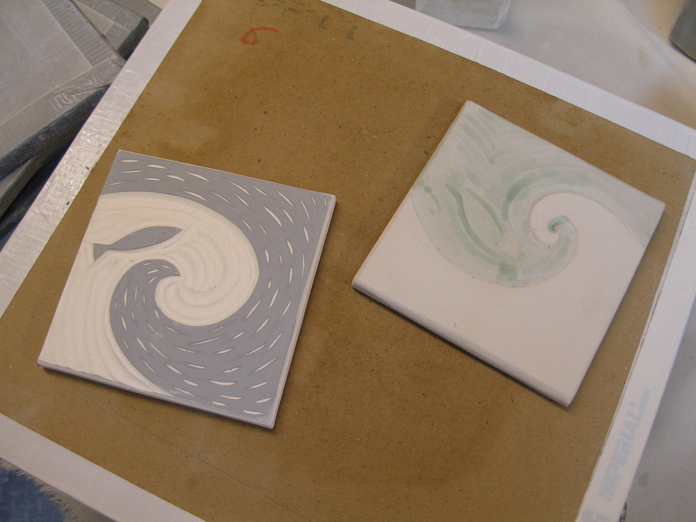 The bisque-fired tile (at left) shows the finished carved image. The light areas are the white-colored clay revealed by carving away the black slip, which now looks grey. The tile is then brushed with various colored glazes (at right) and fired again, for about 11 hours, to 2200°F. The glazes used will give a different effect over the black and white areas.