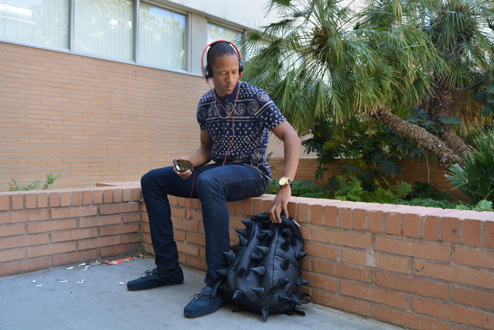 Track and field athlete Van Alexander wears a gold rope chain along with his navy blue bandana print polo, jeans, and Aldo loafers. His accessories include a Diesel watch and Beats by Dre headphones. Photo: Lauren Holmes