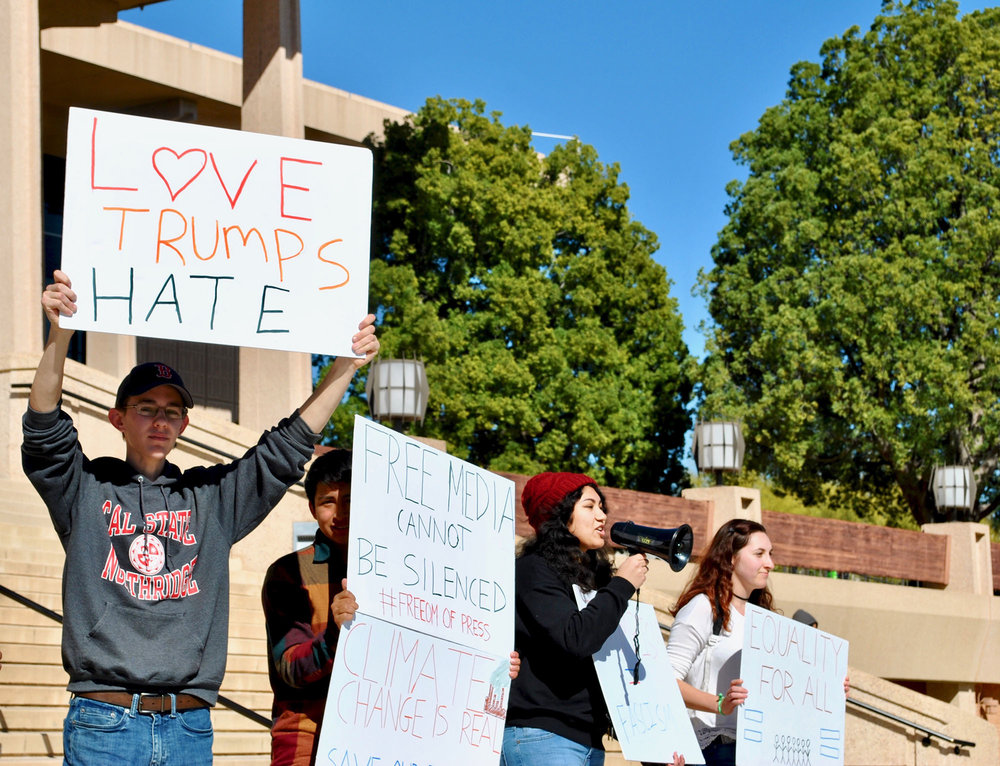 CSUN Young Democrats members John Noone and Kenny Salazar, with two other members, stand in front of the Oviatt protesting the actions on the Trump Administration on Feb. 28. (Photo credit: Brian Andrade)