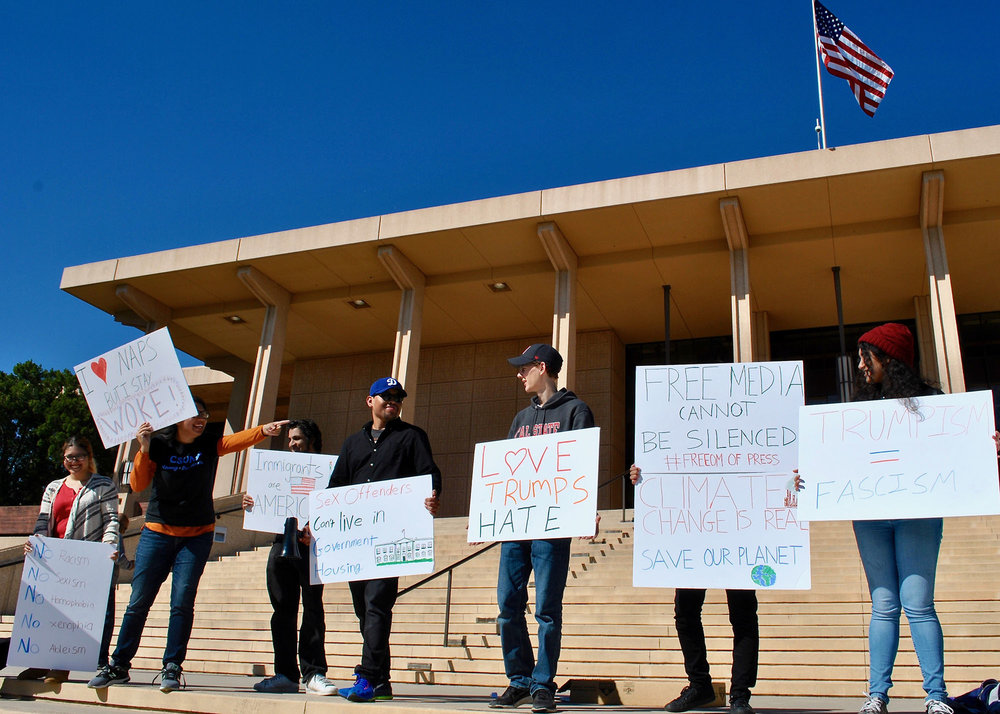 "Onlookers and California Freedom Project demonstrators look on as the CSUN Young Democrats call for ""no hate"" from the Trump administration in regards to his environmental and immigration policies. (Photo credit: Brian Andrade)"