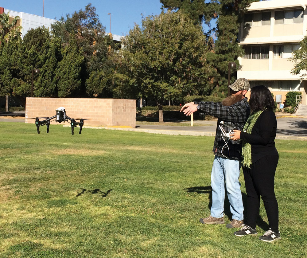 CSUN Geography Club members Dannon Dirgo and Mirna Habib, try out the Inspire Drone during an initial test flight at Sierra Hall. Photo by Amalie Orme.