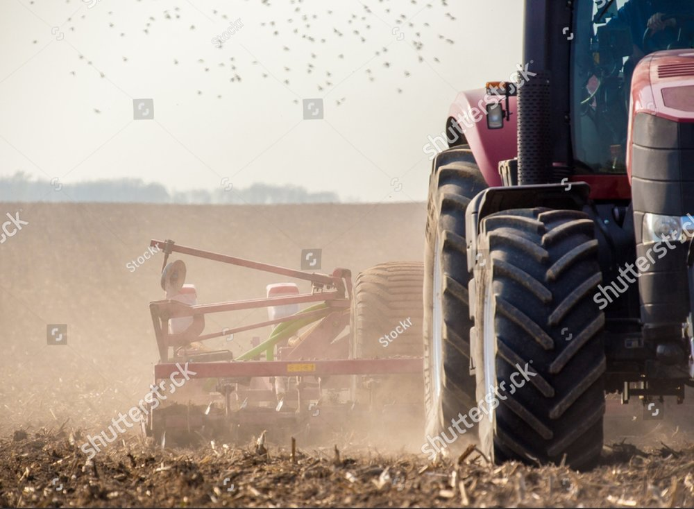 stock-photo-the-tractor-harvester-working-on-the-field-231150910-1.jpg