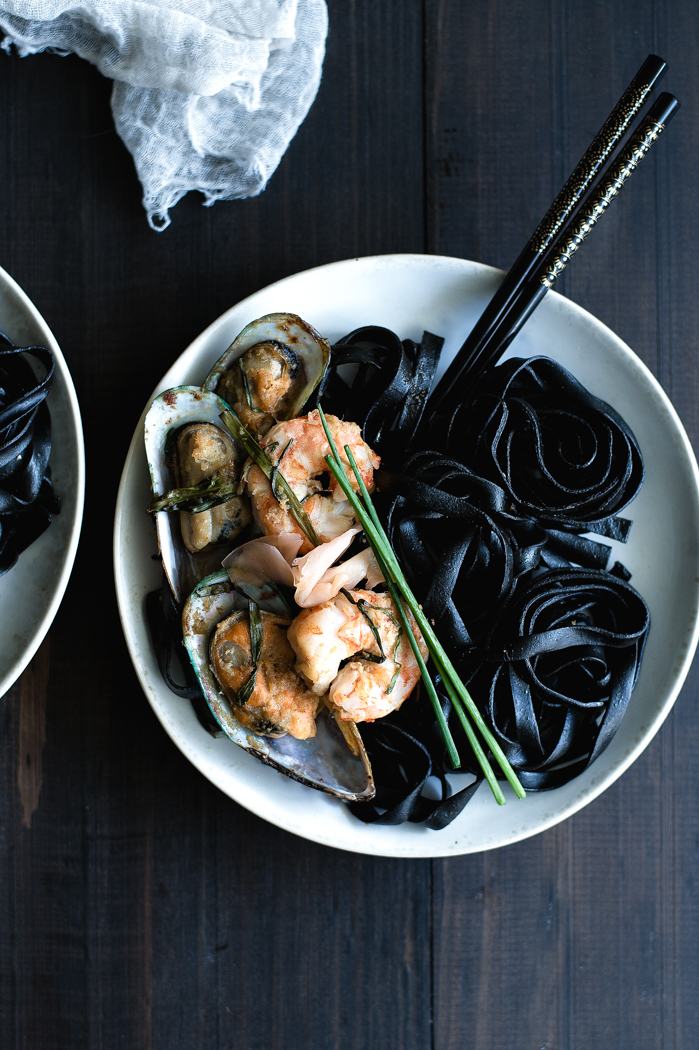 Black Ink Ginger Pasta with Shrimps - SauceChicken broth – 1 cupSoy sauce – 3 TBSPGround ginger – ½ TspFreshly grated ginger – 1 TspFish sauce – 1 ½ TspSriracha sauce (Tabasco for a milder spice) – ½ Tsp or a bit moreFine sea salt – good pinch Roasted seafood Mix of small seafood (mussels, shrimps, scallops, etc.), thawed, washed and prepared to be cook – 1 to 2 poundsGrated ginger – 1 TBSPSesame oil – 2 TBSPRice vinegar – 2 TspFreshly ground garlic – ½ TspSoy sauce – 2 TspFish sauce – 1 TspFine sea salt - ⅛ TspPinch of raw sugarBunch of scallions, roughly choppedBlack ink pastaBlack ink fresh fettuccine – 12 to 16 oz.Fine sea salt – about 4 Tsp