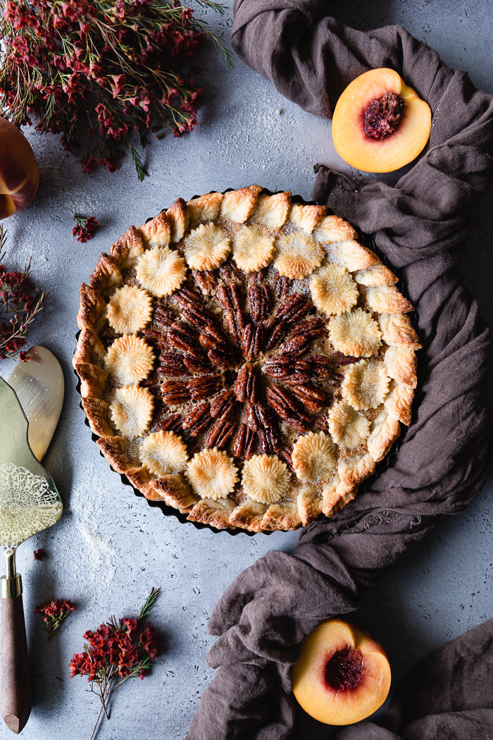 Pecan Pie with Ginger, Cinnamon, Maple and Condensed Milk - Pie crust – 1 for the pie + 1 extra for decorations if desirePecans – 2 cups + about 1 ½ cup of whole pretty pecans for the topCondensed milk – 1 canMaple syrup – ¾ cupDark brown sugar – ½ cupFresh grated ginger (optional) – 2 TBSP approximatelyUnbleached flour – 1 TBSPPure vanilla extract – 2 TspFine sea salt – ¼ TspCinnamon – ¼ TspEggs – 3 at room temperature Raw sugar for sprinkling on top of the pieBeaten egg with a drizzle of water or milk for egg wash