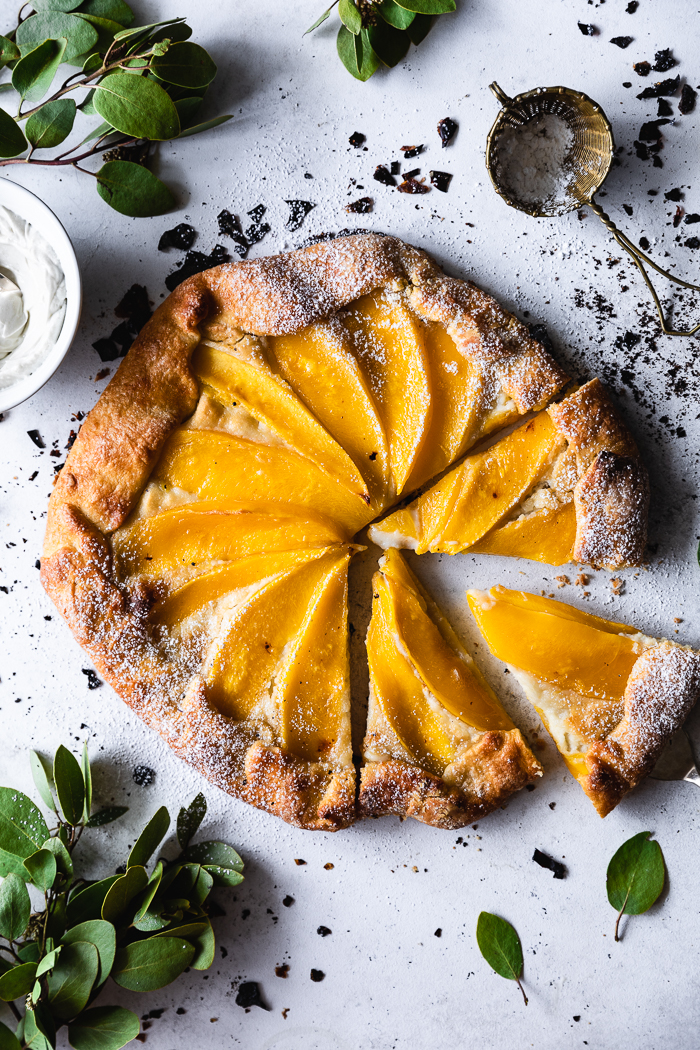 Mango Cream Cheese Crostata - Crust1 disk of this flaky pie crust recipeMango cream cheese fillingFirm mangoes, sliced – 2Raw sugar – ¼ cup for mangos + ¼ cup for cream cheese + 1 TBSP for sprinkling on topMaple syrup (optional) - 1 TBSPCream cheese, at room temperature – 8 oz1 egg, a bit of milk of choice and and a few drops of vegetable oil of choice