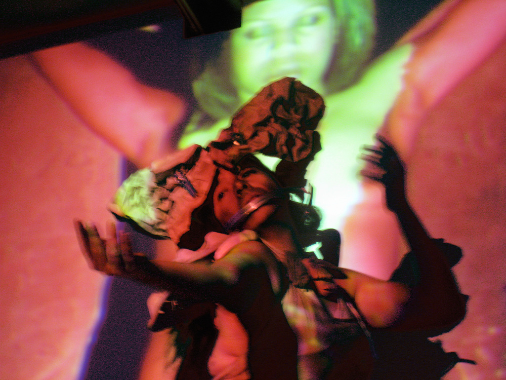Title: Coatlicue, Mi Amor   Medium: Multimedia performance Date: February 2010 Notes: Shondra Mirelle's image is projected against the background while En Dy performs as Coatlicue.