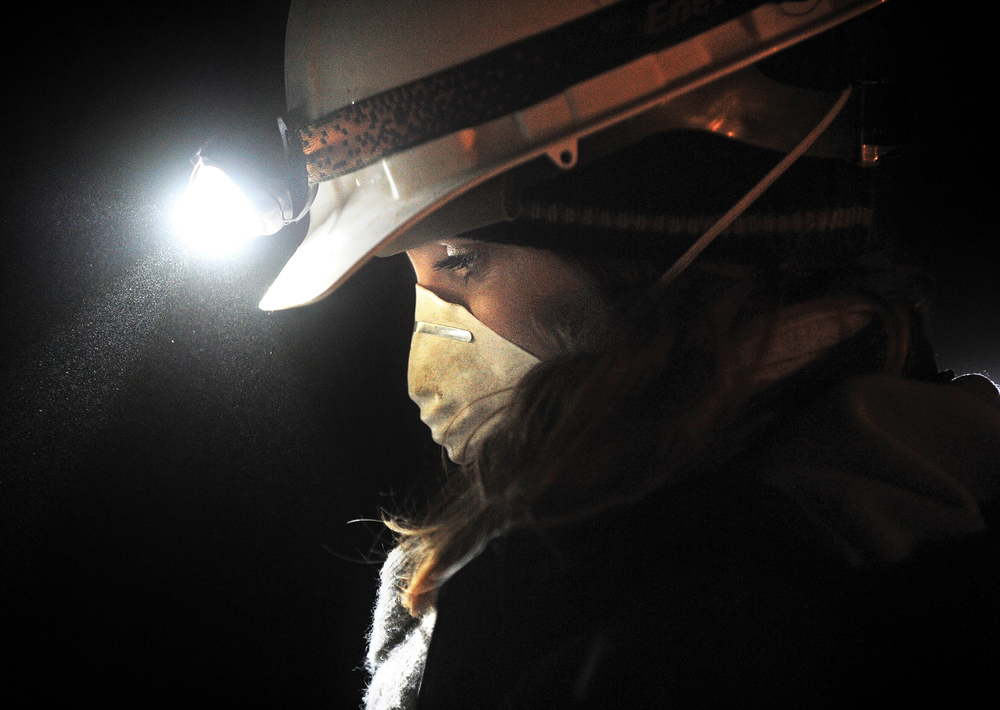 Michelle Carpenter, a senior at Idaho State University studying biological anthropology, uses her headlamp to illuminate an area for measurement Feb. 27 in Dubois.