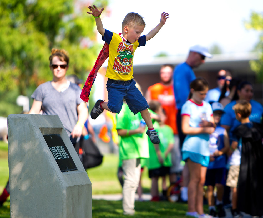Oliver Gadd, 4, jumps off of the Canyon Building sign before the start of the Super Hero Family Fun Run on Saturday, Aug. 26, 2017, during Kid's Fest at the College of Southern Idaho Herrett Center in Twin Falls Idaho. The run was a one-mile lap around campus and participants were encouraged to dress as their favorite super hero.
