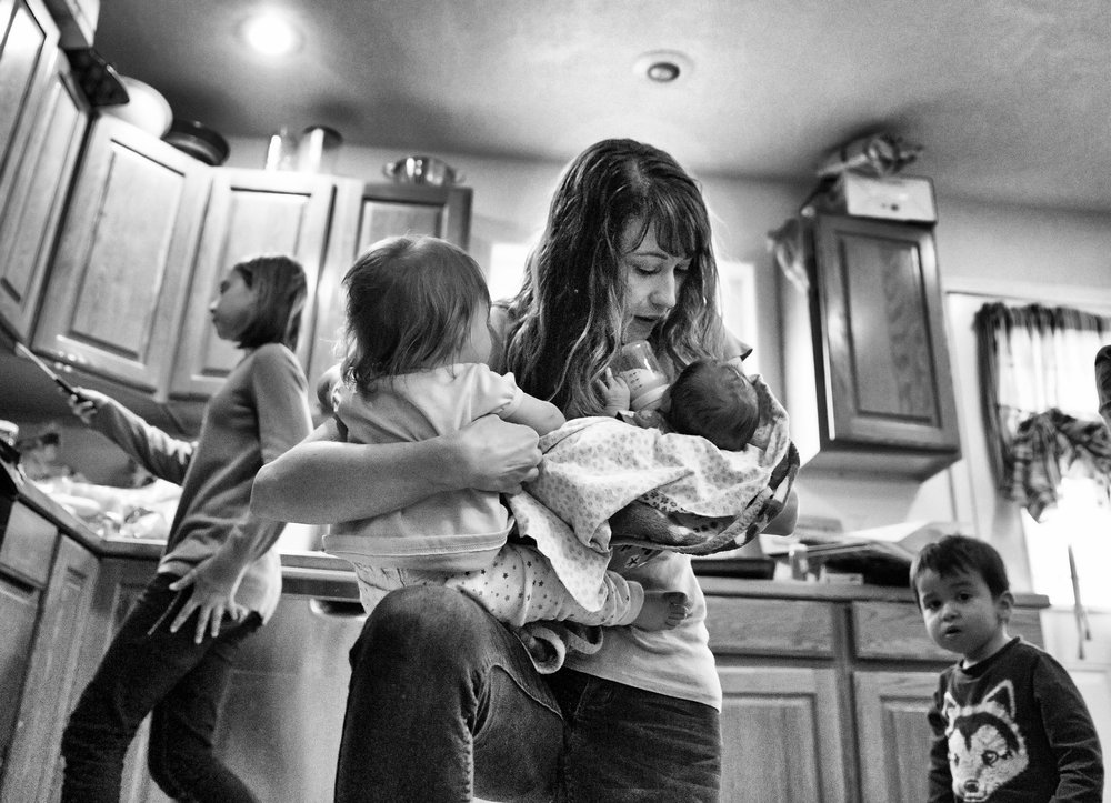 Anne Sharp holds two of her foster children as her daughter Jordyn, left, cleans up the kitchen and her son Zayden, right, searches for his water cup Friday, April 7 2017, at their home in Jerome Idaho. Sharp says she's been a foster parent for 10 years. She currently has seven children in her house ranging from 11 years old to 12 days old. 'We never planned on seven, but that's how it worked out,' she says.