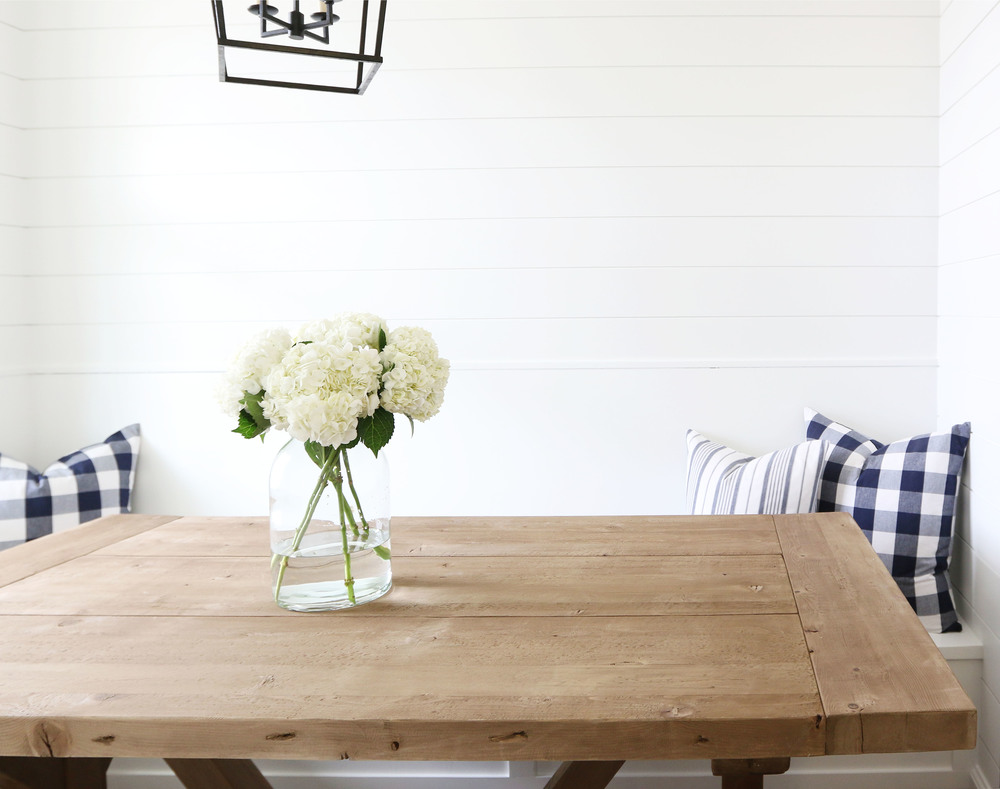 Reclaimed wood table and navy buffalo check pillows || Studio McGee
