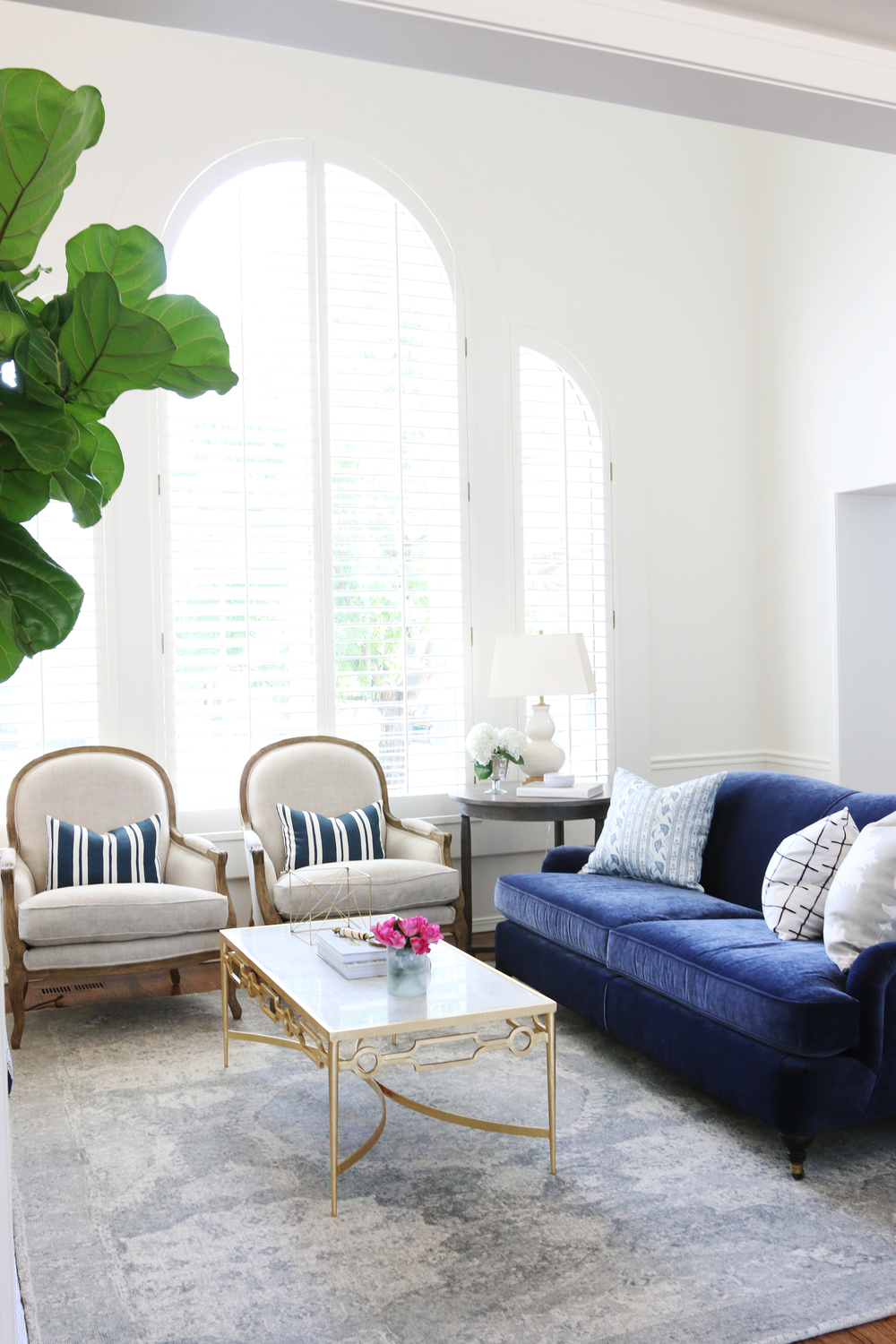 Blue couch and white chairs with blue & white striped pillows