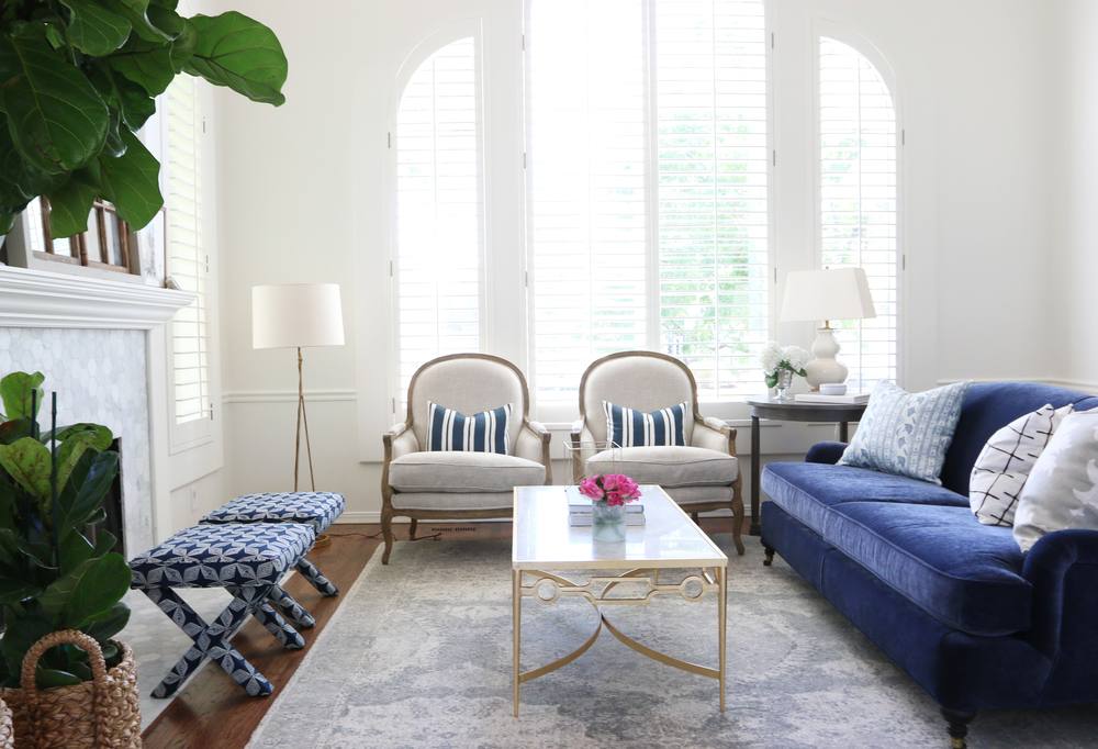 Living room with blue couch and white chairs