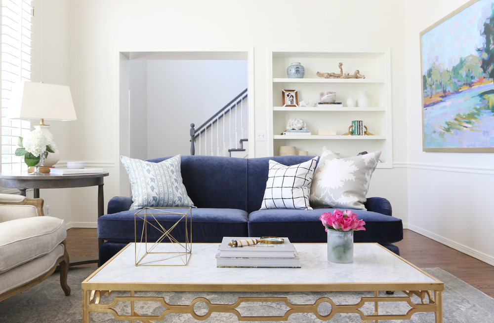 Blue couch with decorative pillows and built-in wall shelves