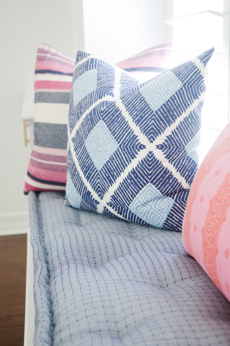 Blue and pink decorative pillows on window bench