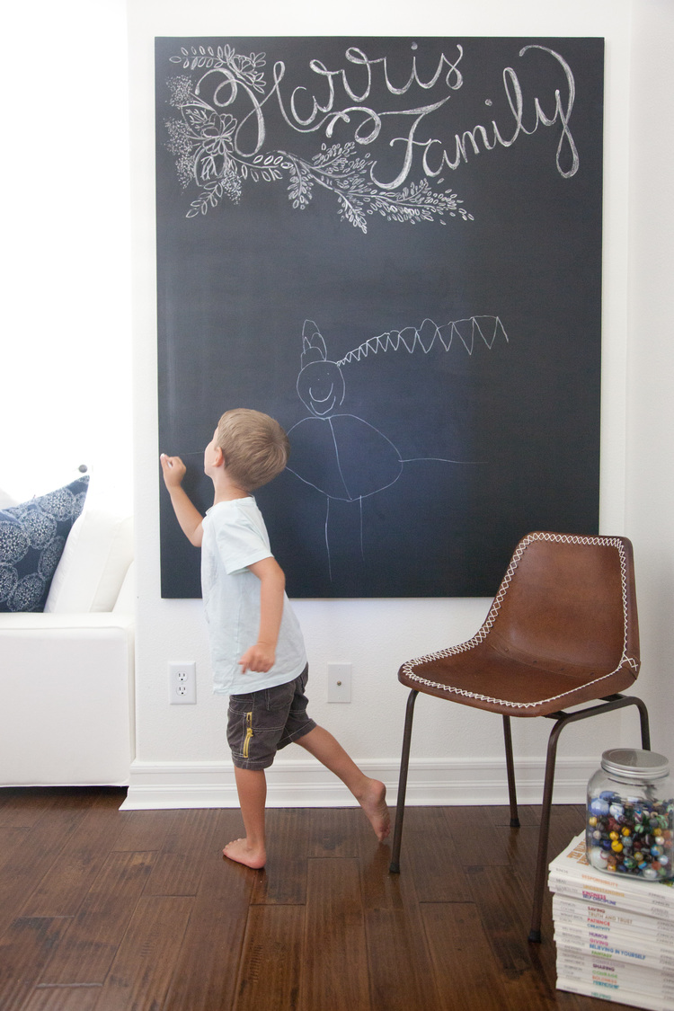 Young boy writing on blackboard in activity room