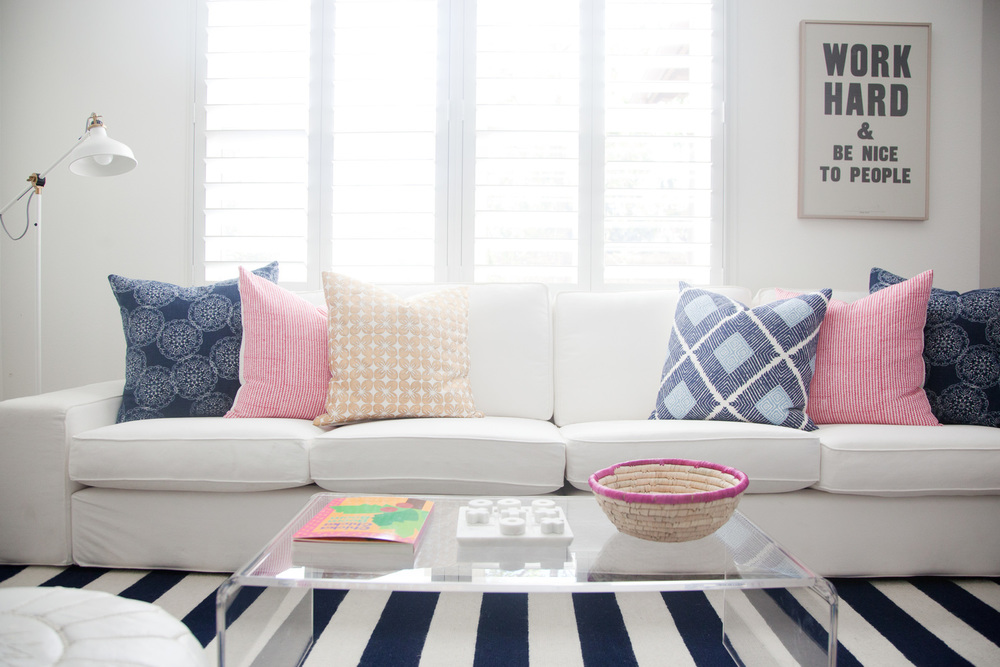 living room design with white couch, striped rug, and decorative pillows