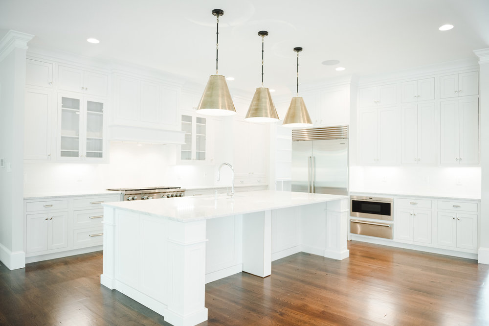 White kitchen with dark floors and brass pendants by Studio McGee