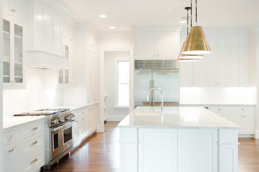 Renovated kitchen with marble counters and overhanging lights