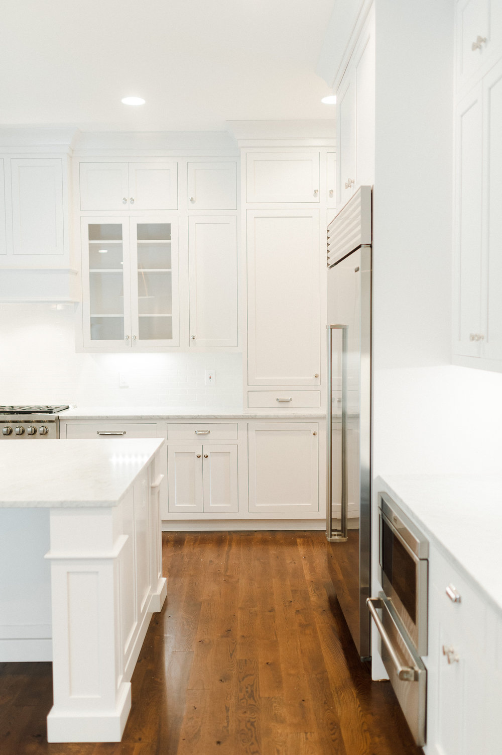 White kitchen cupboards and cabinets with stainless steel refrigerator