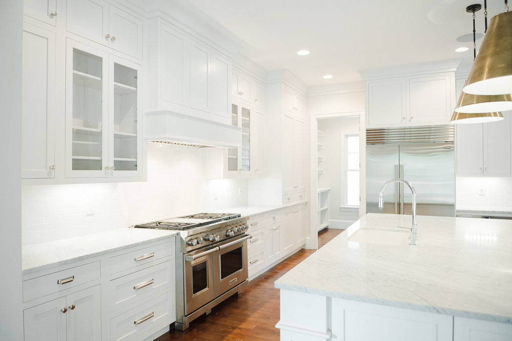 White kitchen with marble counter tops and stainless steel oven