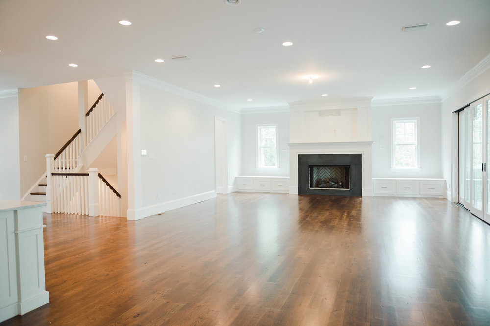 Renovated living room with white walls and hard wood floors