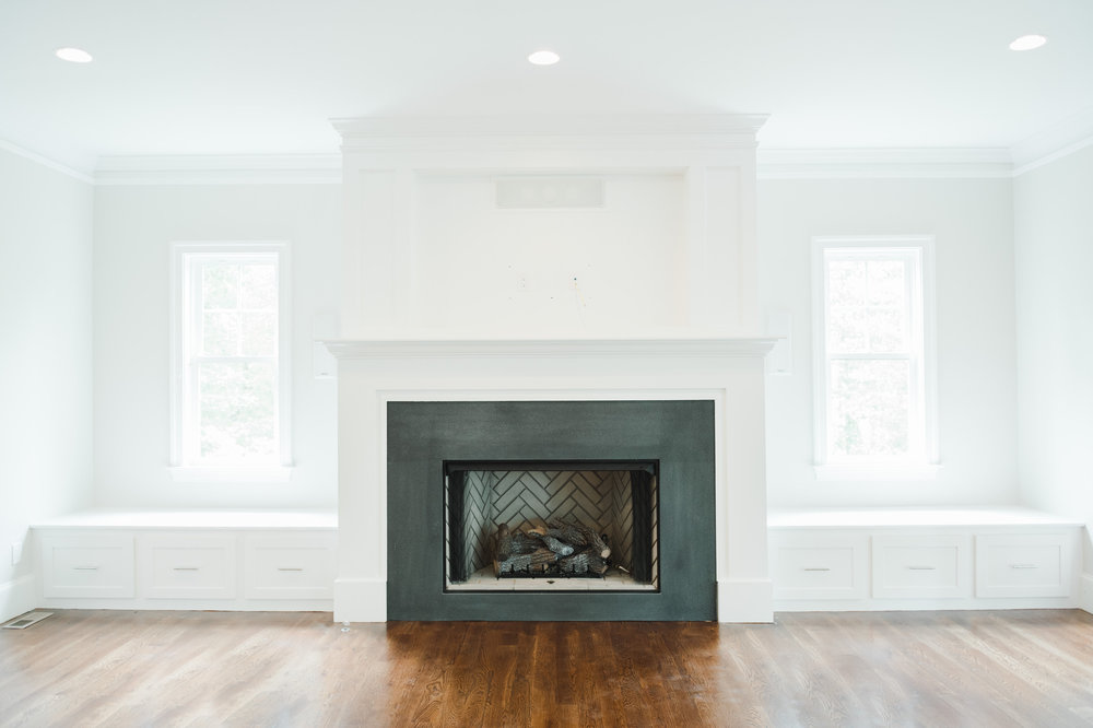 Dark fireplace with white molding and hard wood floors