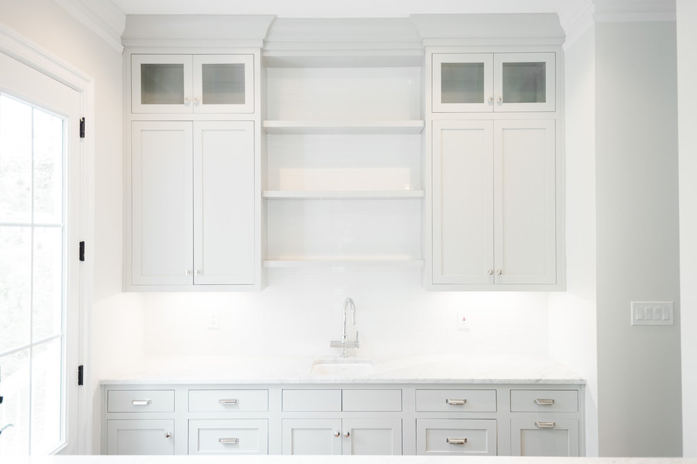 Built-in cupboards and shelves above counter with sink