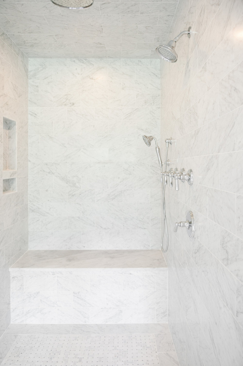 Marble shower interior with shower head, shower hose, and bench