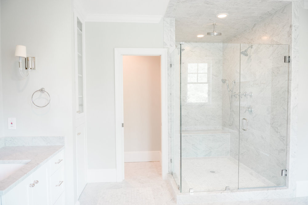 Marble shower with glass doors and built-in bench