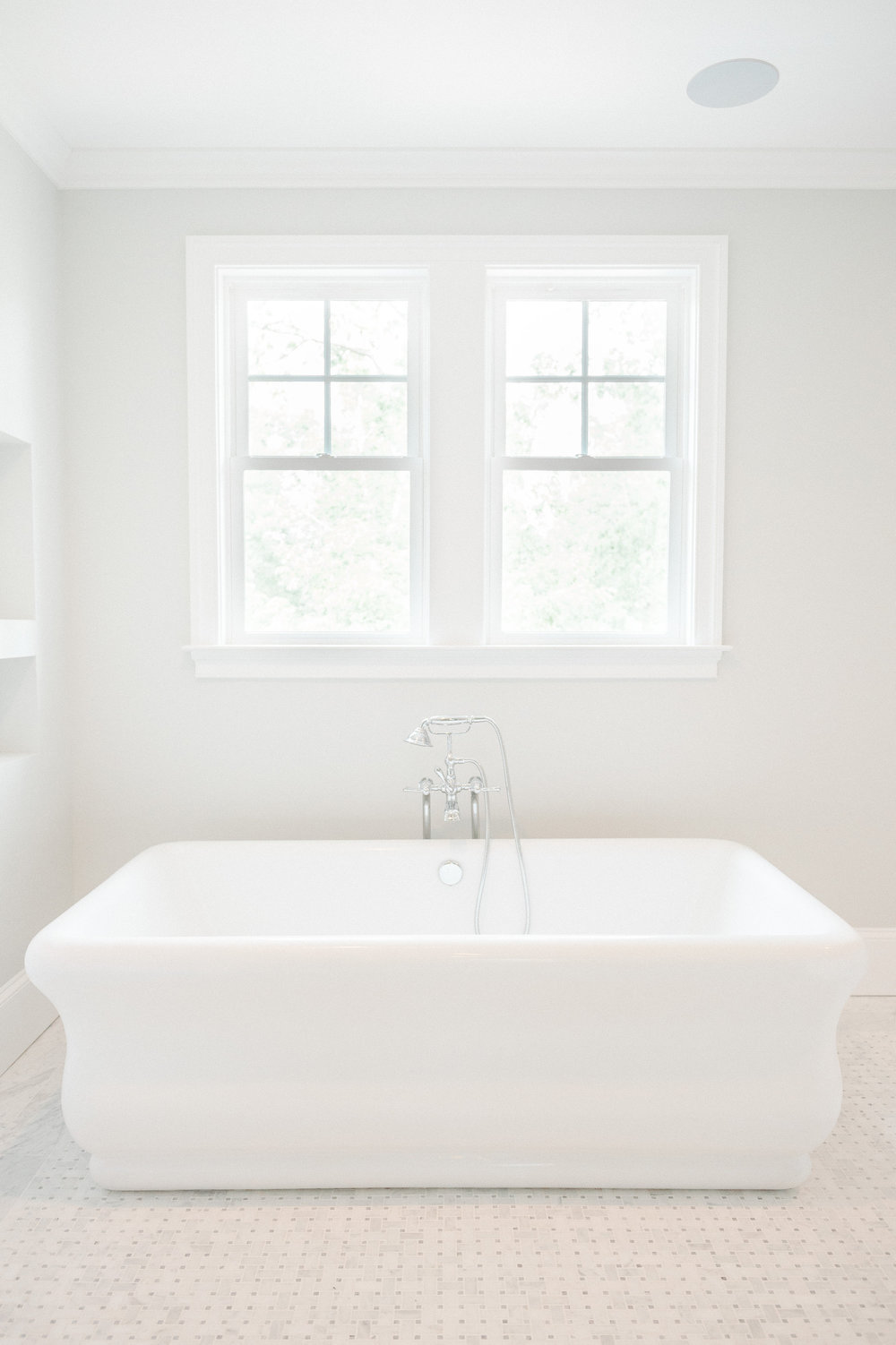 Freestanding white bathtub with shower hose