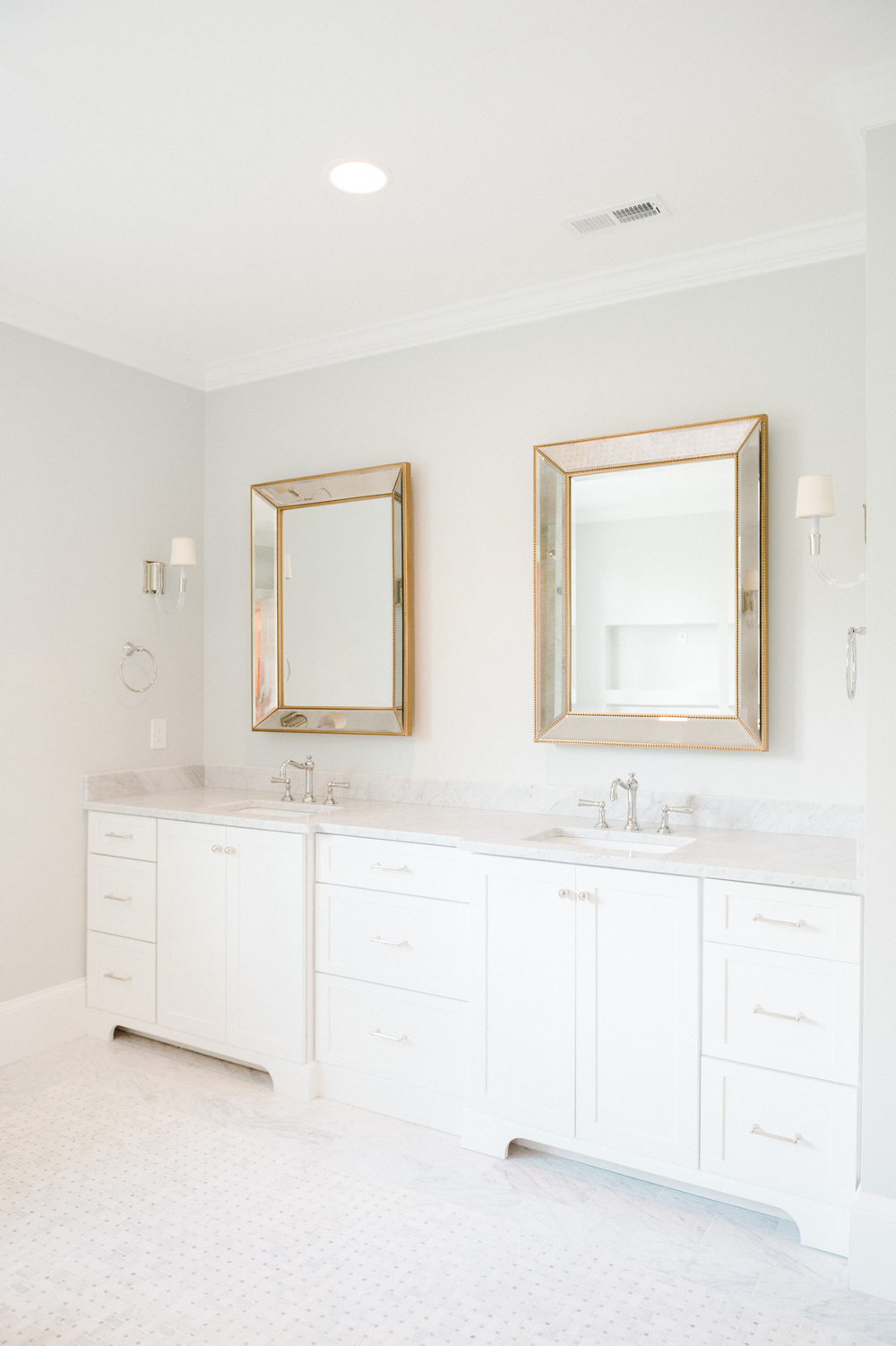 Master bathroom double sinks, marble counters, and gold-trimmed mirrors