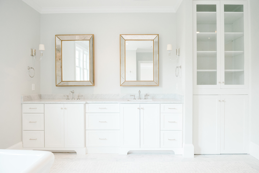 Double bathroom sinks with two mirrors and glass linen closet